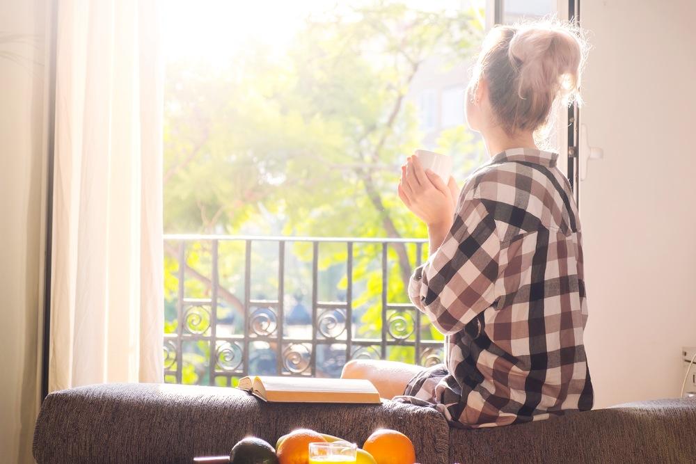 自宅の窓辺に座り飲み物を飲んでリラックスする女性