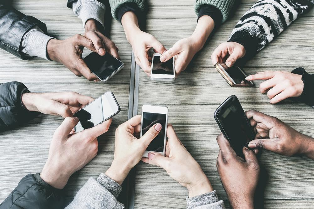 スマートフォンを持って集まる人々