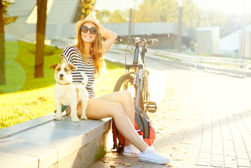 犬を連れて自転車で散歩するサングラスをかけた女性