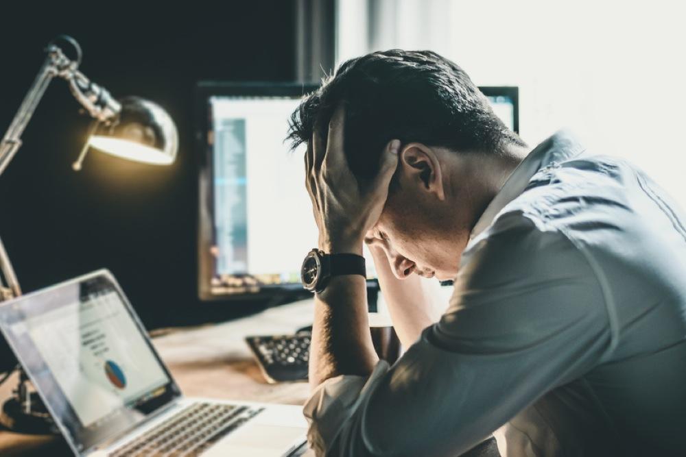 暗いオフィスで頭を抱えて悩む男性