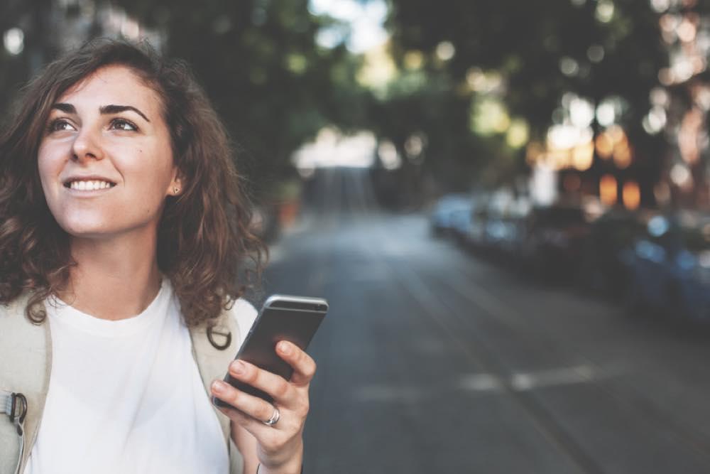 スマートフォンを持って景色を楽しむ女性