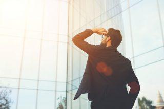 太陽を眩しそうに見上げる男性