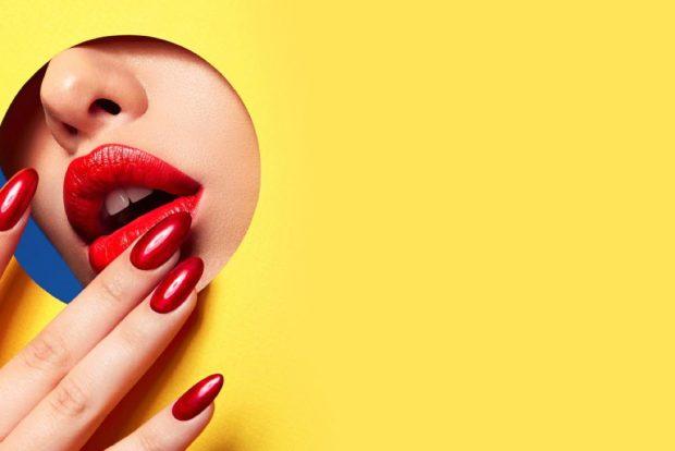 赤い口紅をつけた唇と、真っ赤なネイルの手