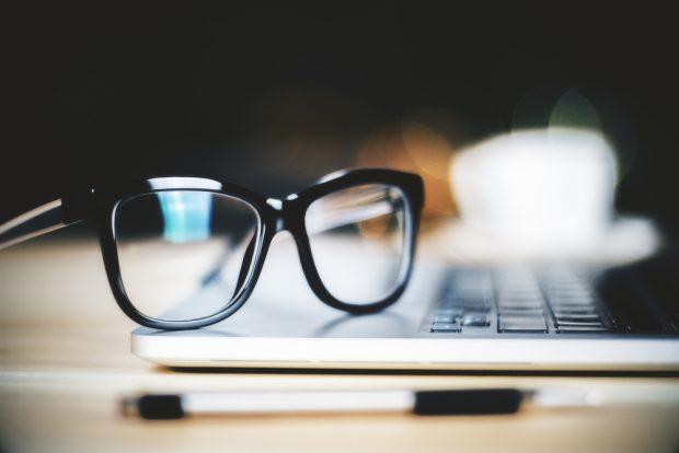 開いたノートパソコンの上に置かれたメガネ