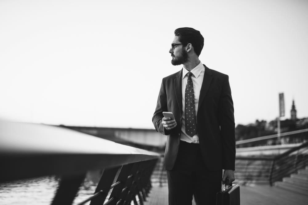 海を見つめるスーツ姿の男性の白黒写真