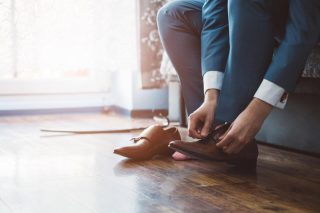 革靴を履こうとしているスーツ姿の男性