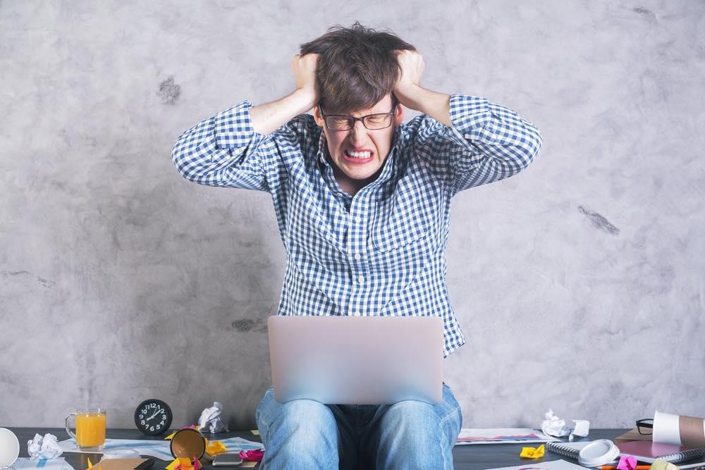 ノートパソコンを膝に乗せ、髪をグシャグシャにしながら苦しい表情をする男性