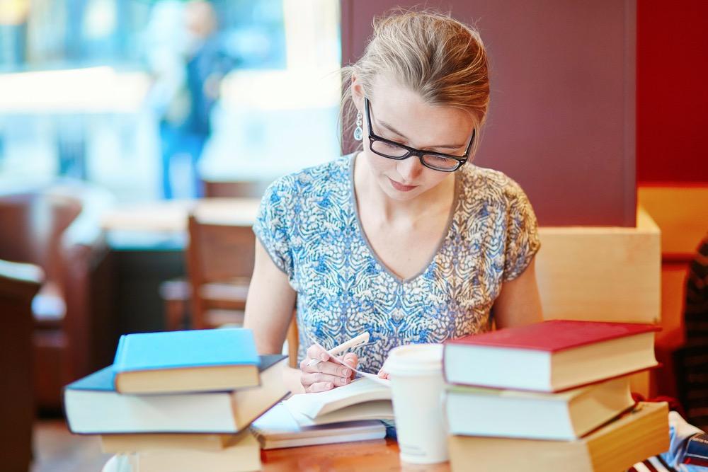 本を机に山積みにしながら勉強する女性