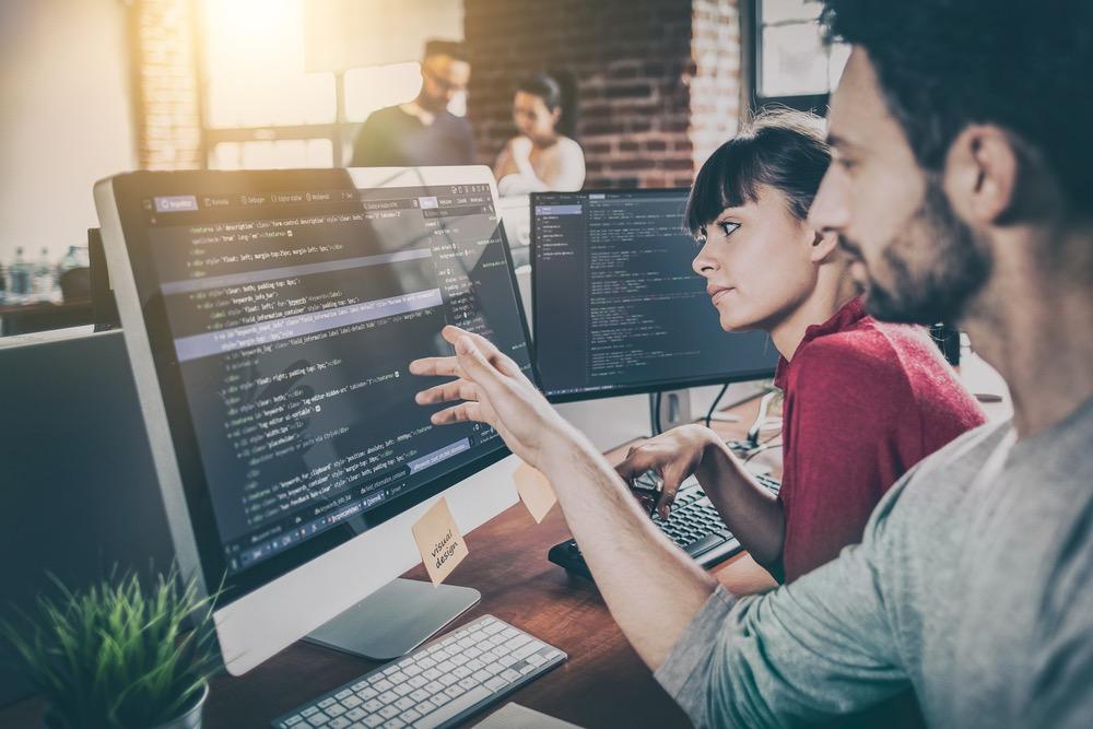 プログラム用のエディタ画面を見ながら仕事をする人々