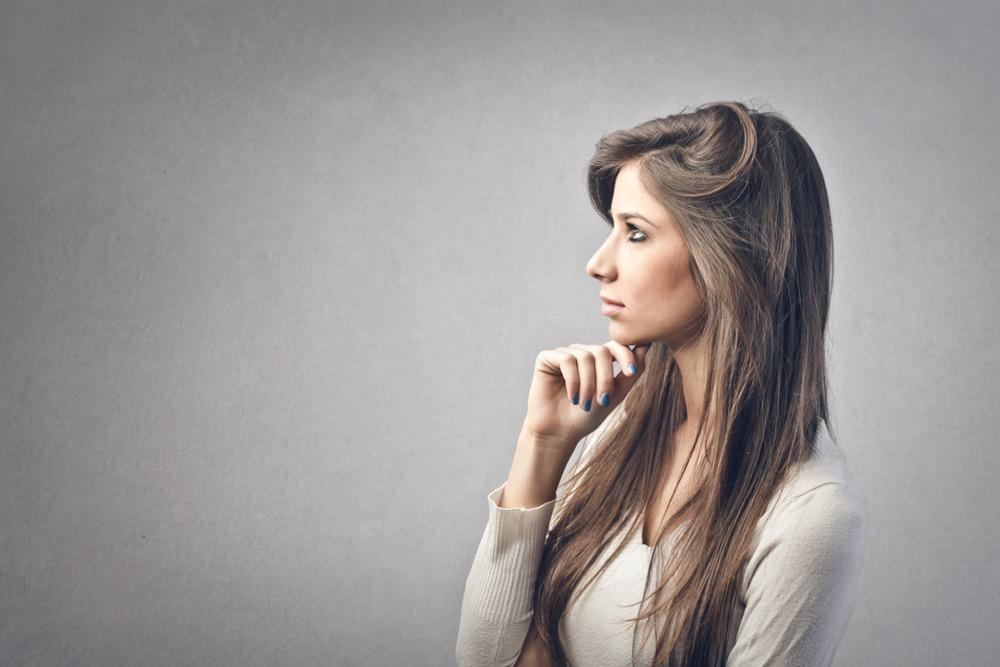 顎に手を当てて考える女性