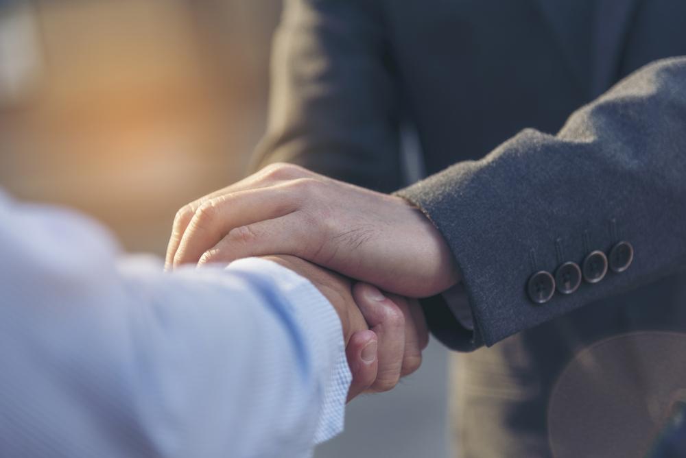 再び営業職に就職し、握手を交わす男性