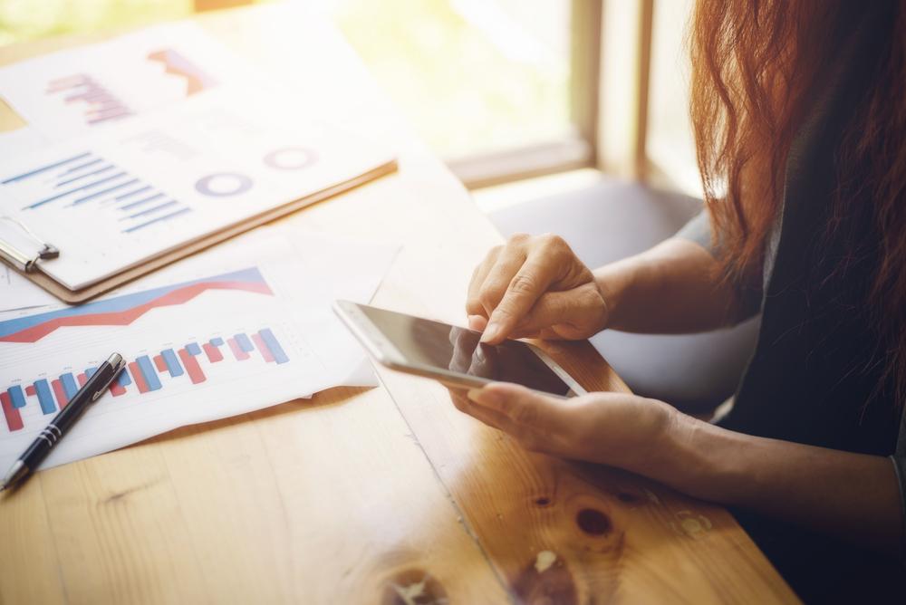 データが書かれた書類を広げながら携帯を触る女性