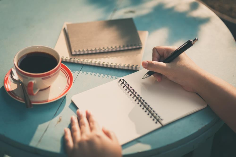 コーヒーを飲みながら机の上でノートにメモを取ろうとしてる様子