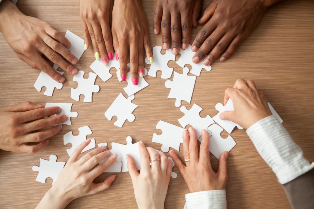 数人でパズルのピースを合わせている