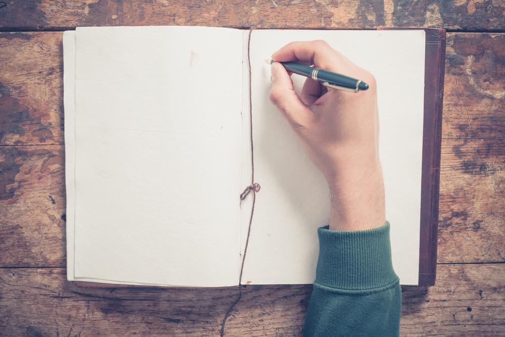 本に文字を書こうとしている手