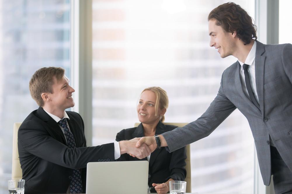 空白期間を上手に伝え、内定を獲得し社員と握手しているフリーターの男性