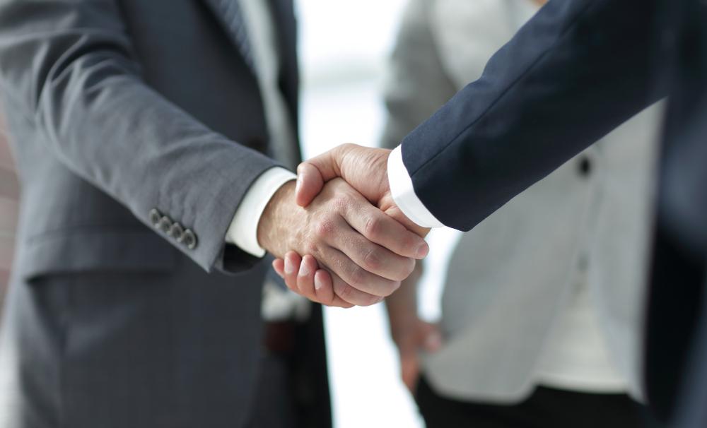 就職支援サービスのカウンセラーと握手するフリーターの男性